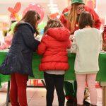 Evento Conad, addetta al tavolo bimbi con tre bambini di spalle in primo piano