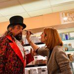 Evento Conad, attore con cappello a cilindro e giacca velluto rossa e nera maculata intento al trucco