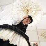 Evento Conad, una ragazza sui trampoli con vestito nero, bombetta e ombrellino