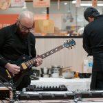 Evento Conad, artista intento a provare la chitarra elettrica
