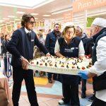 Evento Conad - una torta di grandi dimensioni con panna e frutta sorretta da 3 persone