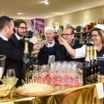 Evento Conad - 5 persone brindano con calici di vino bianco in mano