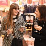 Evento Conad - due ragazze sorridenti con bicchiere di vino in mano