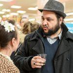 Due partecipanti all'evento Conad, uomo giovane con cappello in primo piano che parla con una donna