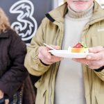 Un uomo in primo piano e una donna sullo sfondo partecipanti dall'evento Conad. L'uomo ha un piatto con una torta di frutta.