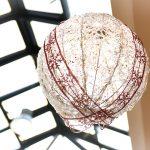 Decorazione natalizia con boccia luminosa fatta di legno intrecciato con barra