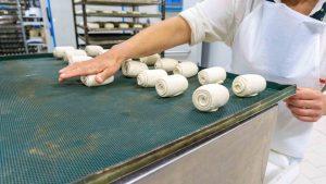 Una immagine di addetta al reparto forno nella produzione del pane